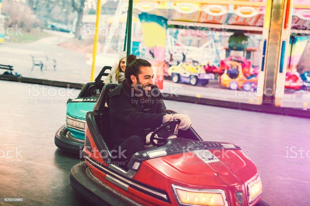 Couple Having Fun Riding Bumper Cars. stock photo