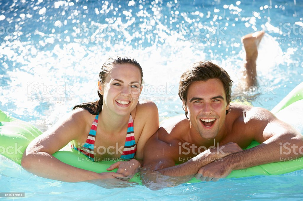 Couple Having Fun With Inflatable Airbed In Swimming Pool royalty-free stock photo