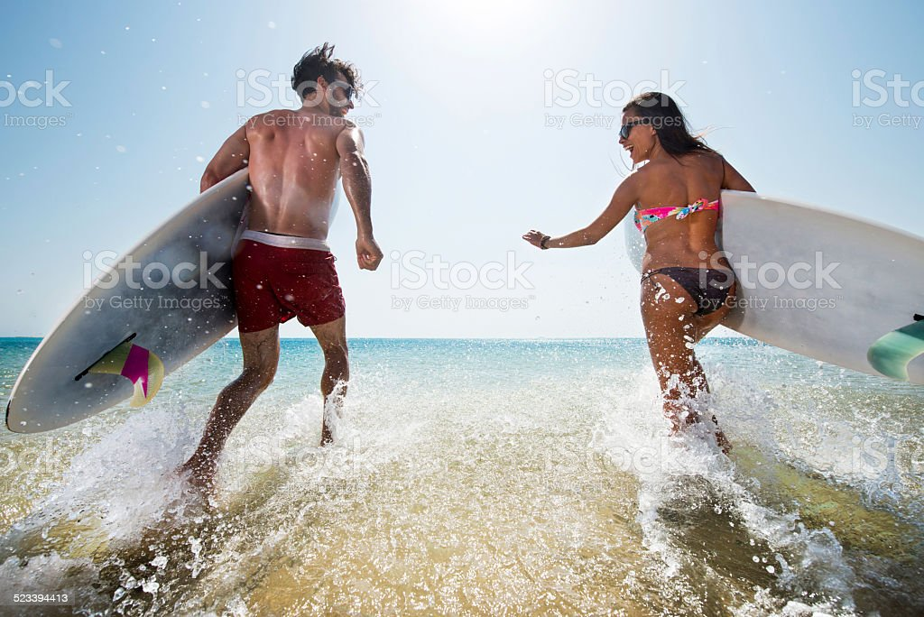 Couple having fun with surfboards. stock photo