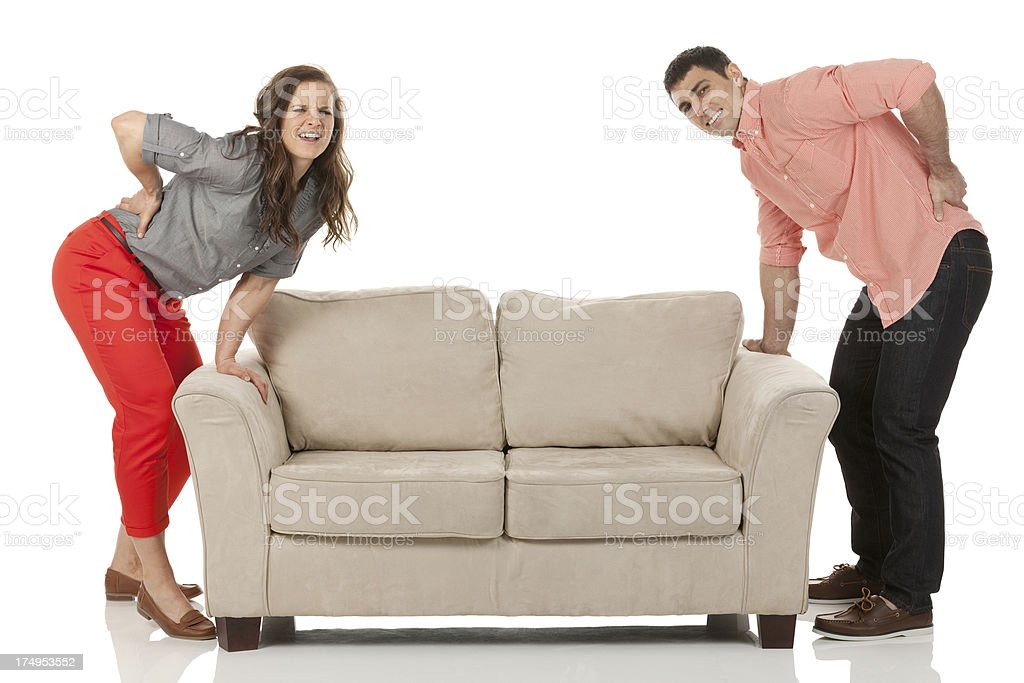 Couple having pain during lifting a couch royalty-free stock photo