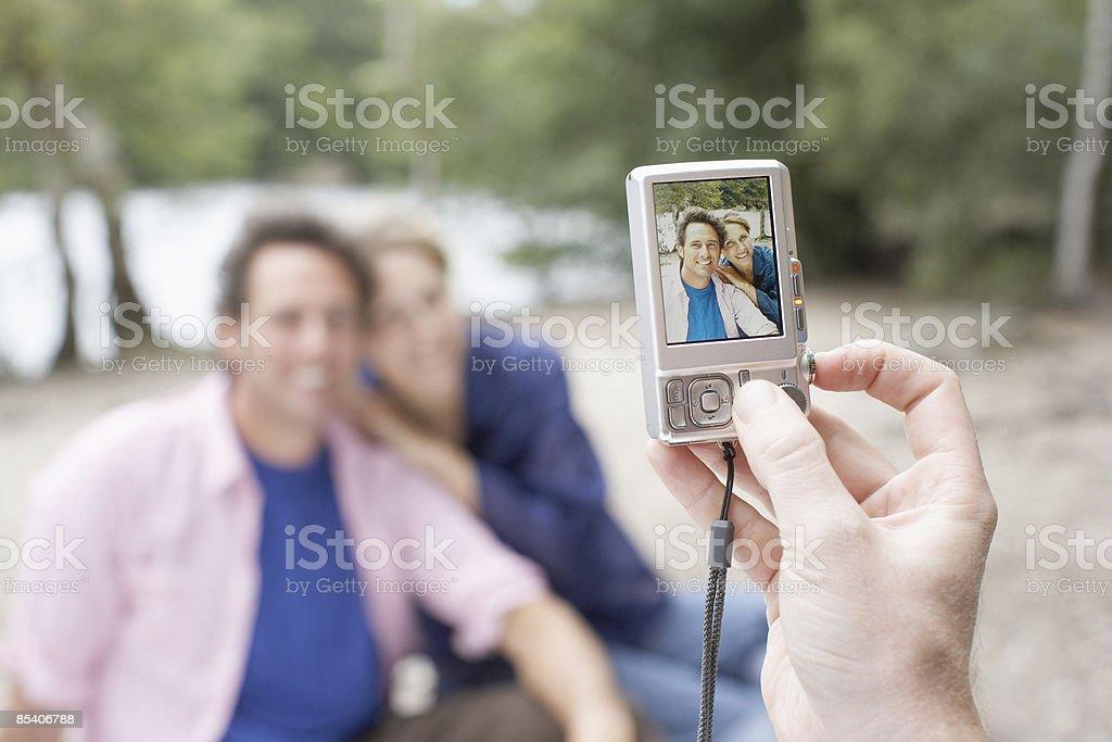 Couple having photograph taken with camera stock photo