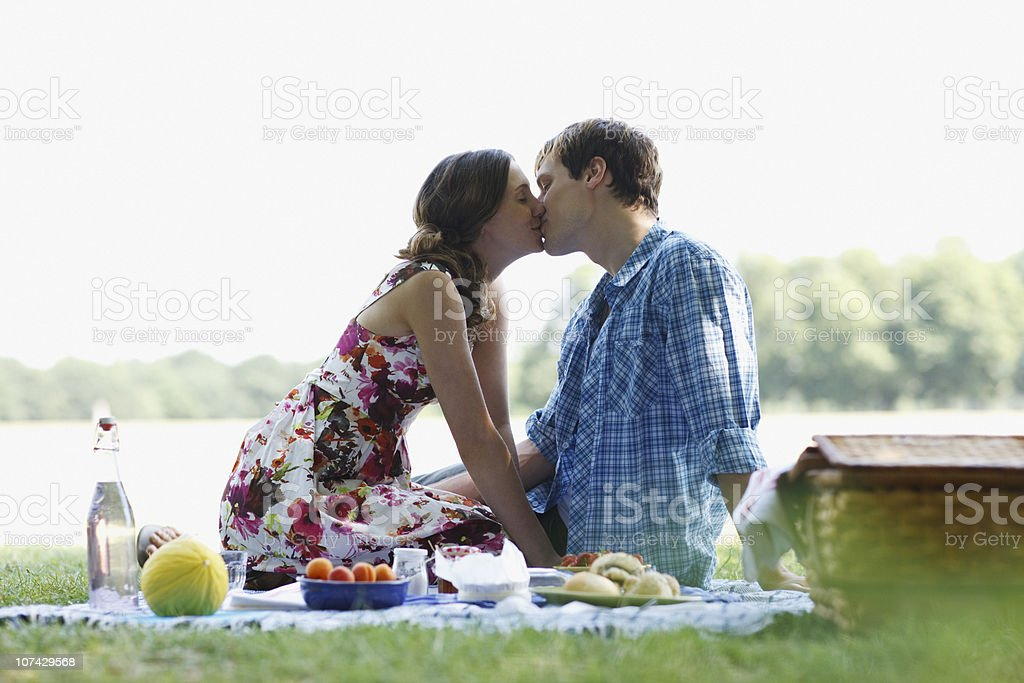 Couple having picnic in park and kissing royalty-free stock photo