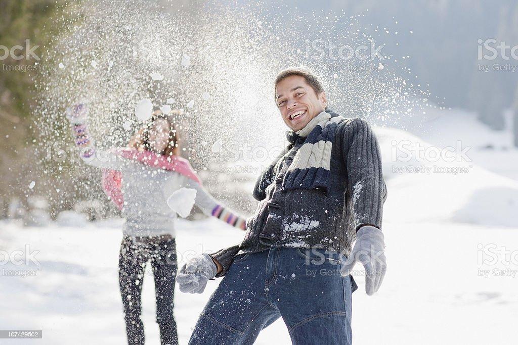 Couple having snowball fight royalty-free stock photo
