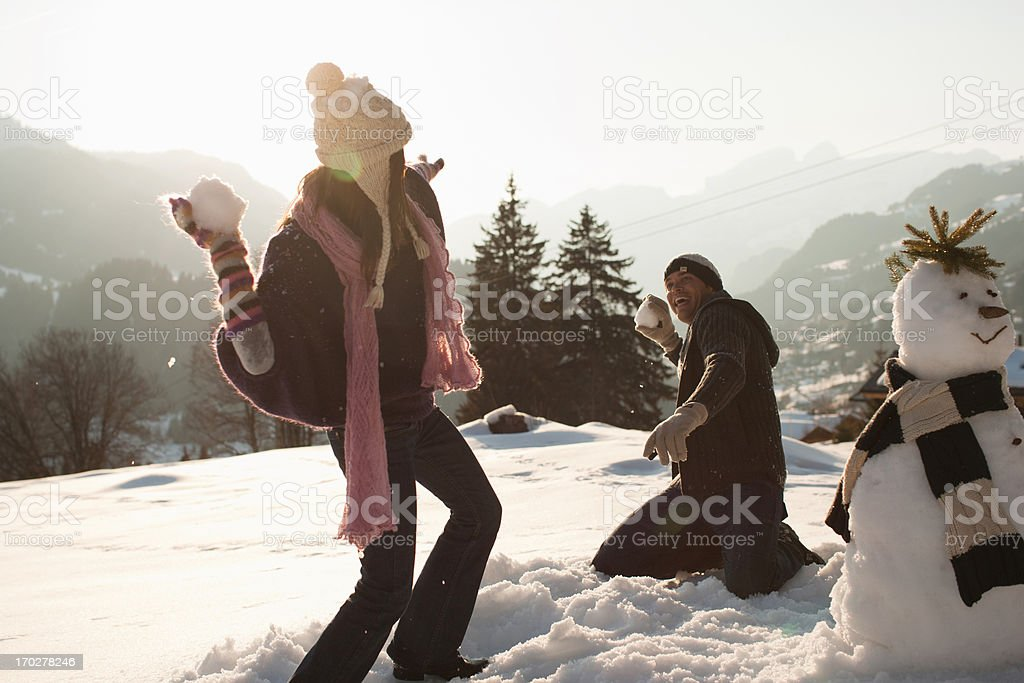 Couple having snowball fight stock photo