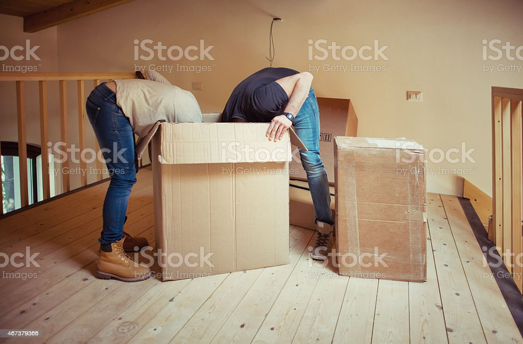 Couple having their heads inside a moving box during a move stock photo
