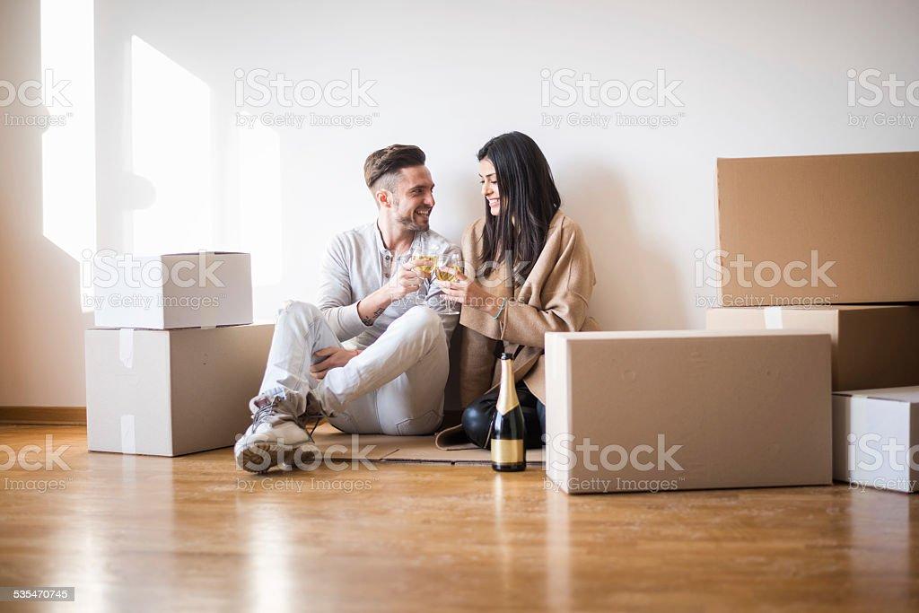 Couple having toast on the floor of new apartment stock photo