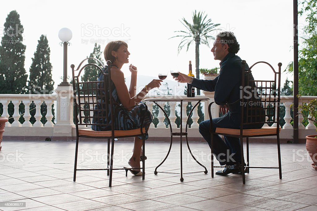 Couple having wine on balcony stock photo