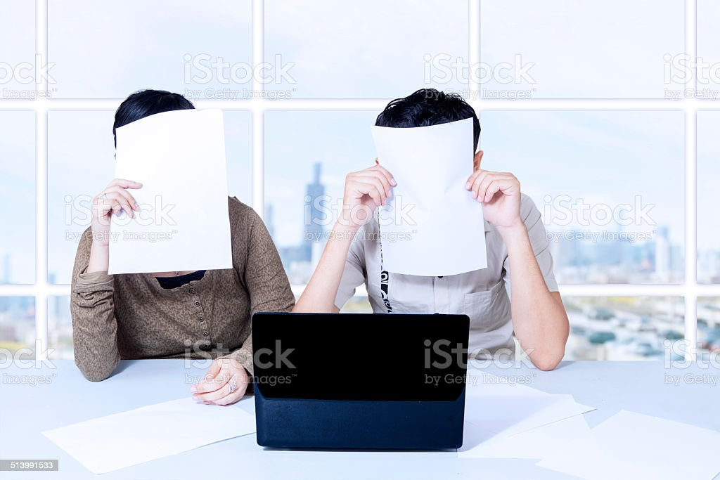 Couple hiding behind papers sitting with laptop stock photo
