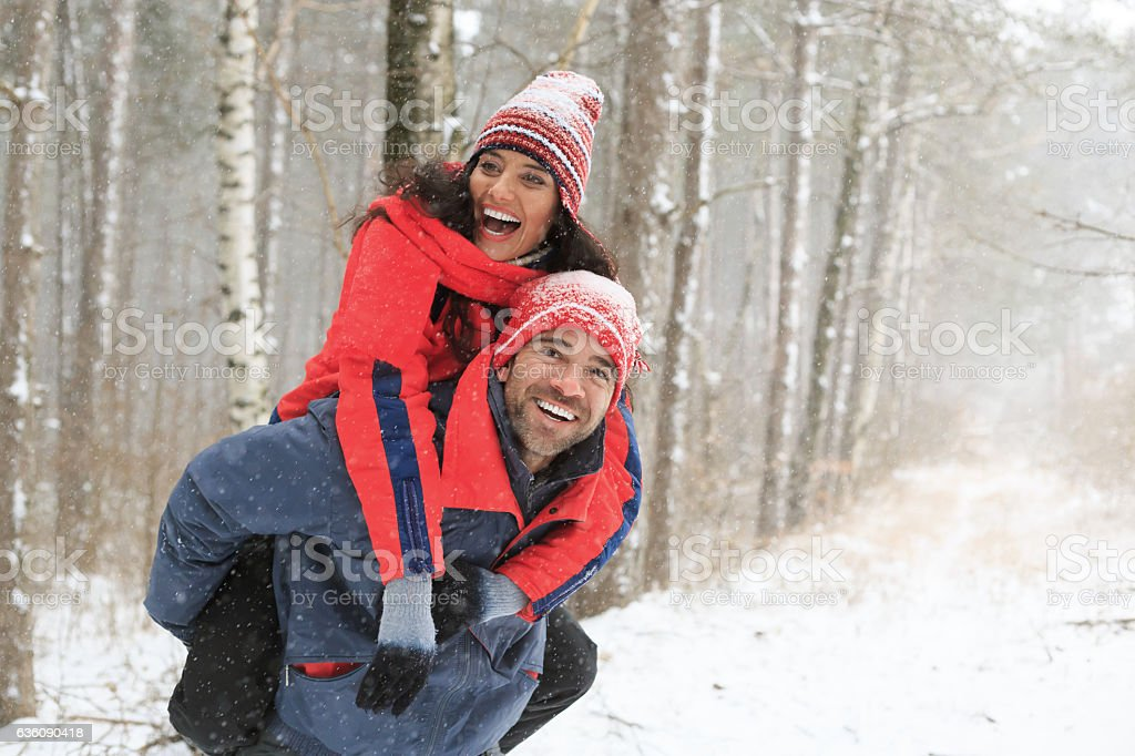 Couple hikers having fun in piggyback ride in snow forest stock photo