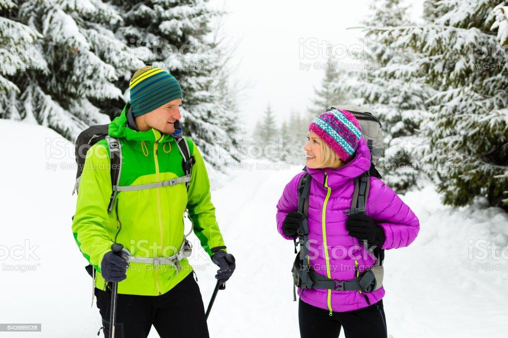 Couple hikers trekking on snow in winter woods stock photo