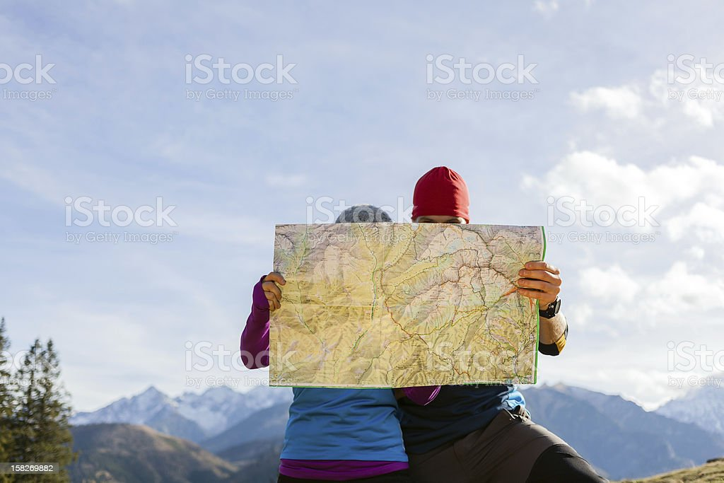 Couple hikers with map in mountains stock photo