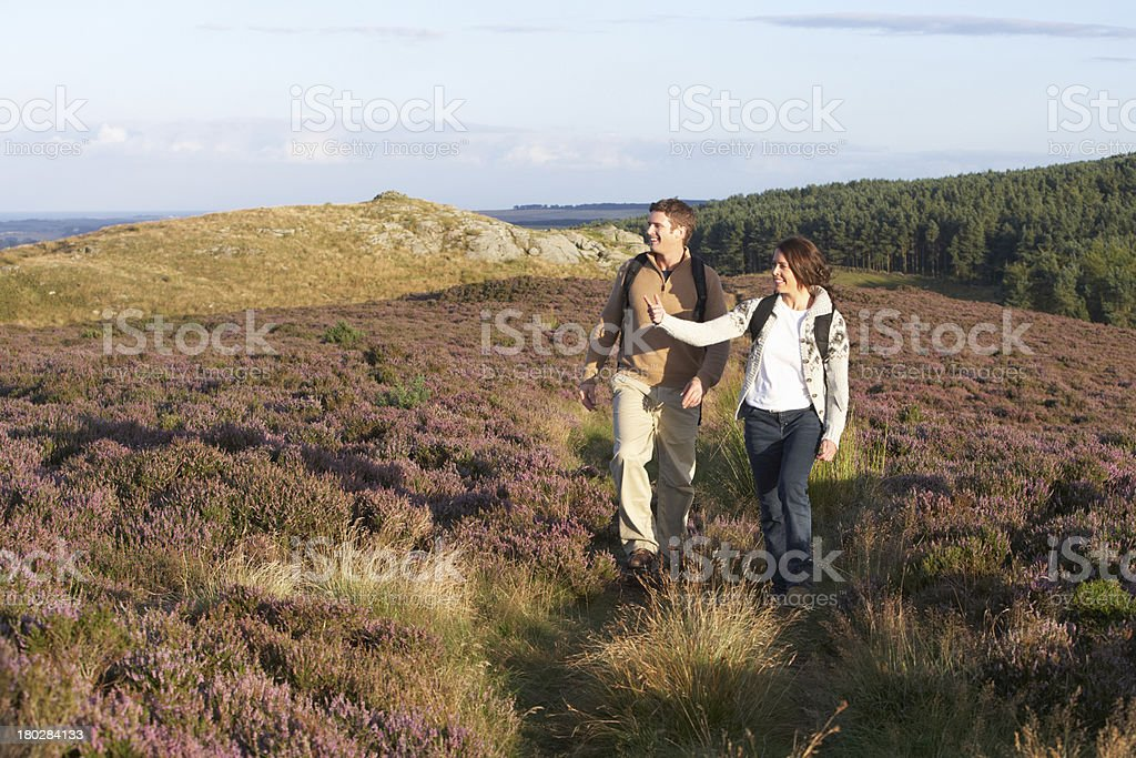 Couple Hiking Across Moorland Covered With Heather royalty-free stock photo