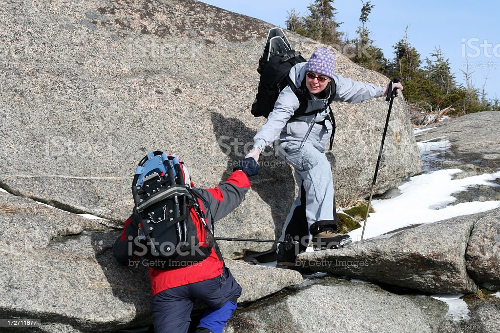 Couple Hiking and Helping Each Other to Climb royalty-free stock photo