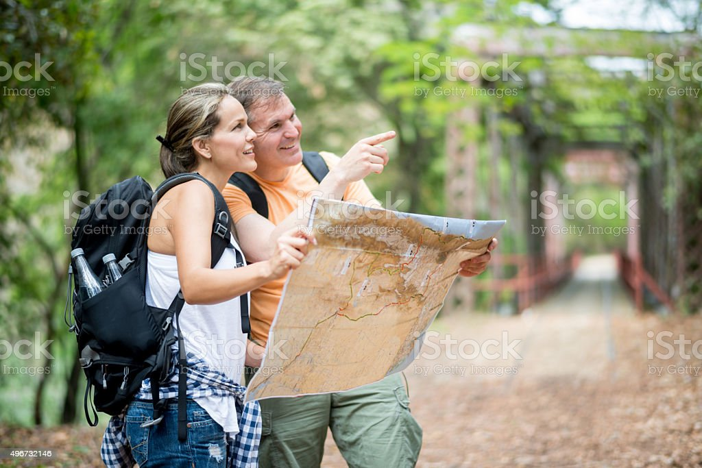 Couple hiking and holding a map stock photo