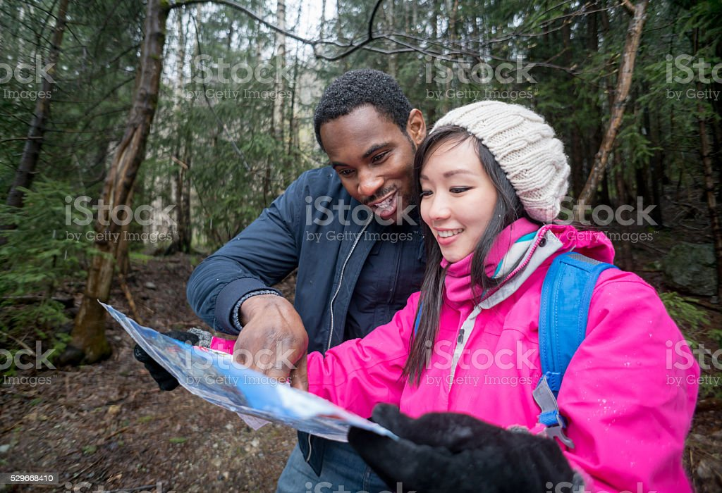 Couple hiking and looking at a map stock photo
