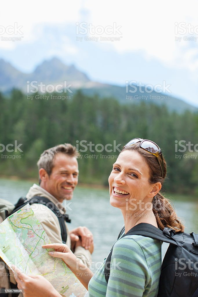 Couple hiking and looking at map in remote area stock photo
