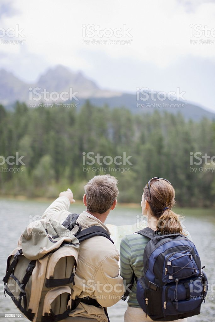 Couple hiking and looking at map in remote area royalty-free stock photo