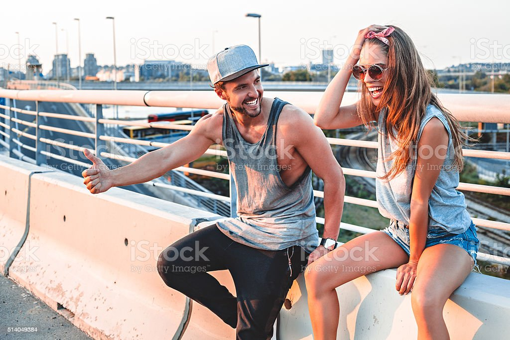 Couple hitchhiking and laughing stock photo