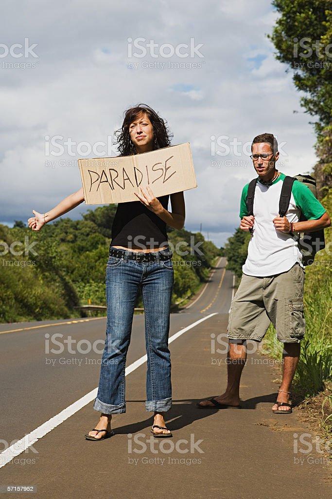 Couple hitchhiking stock photo