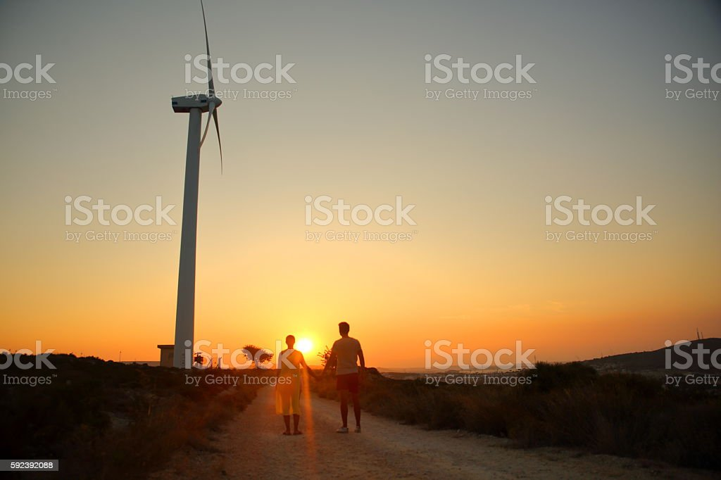 Couple hold hands on Wind turbine stock photo