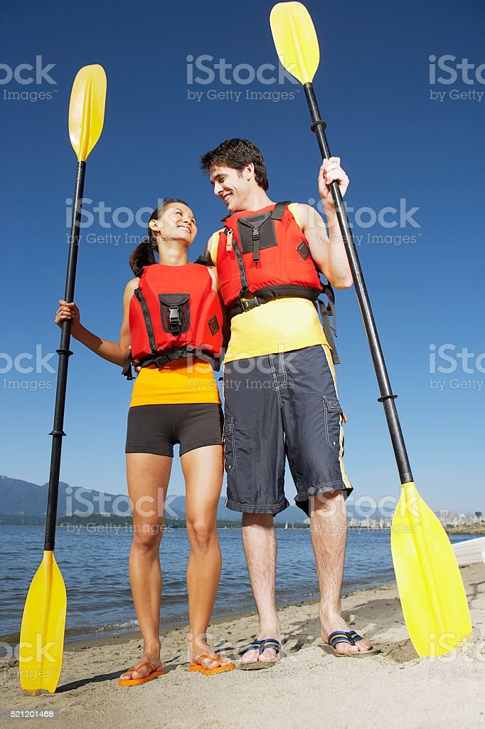 Couple holding boat oars stock photo