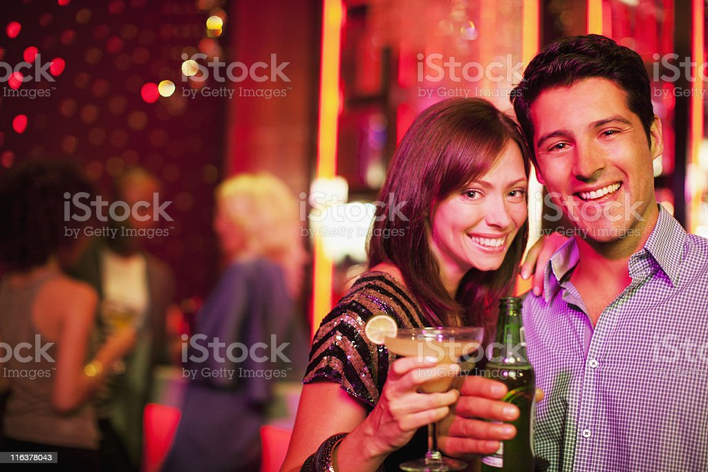 Couple holding drinks in nightclub royalty-free stock photo