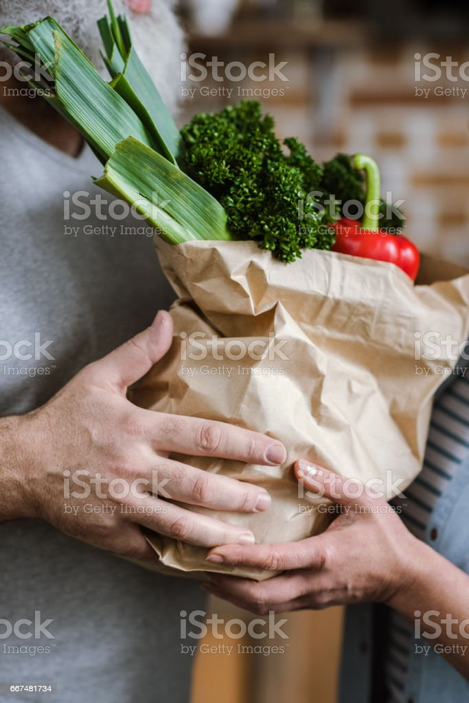 Couple holding fresh vegetables stock photo