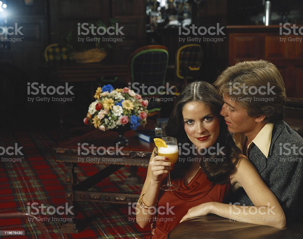 Couple holding glass of cocktail, smiling royalty-free stock photo