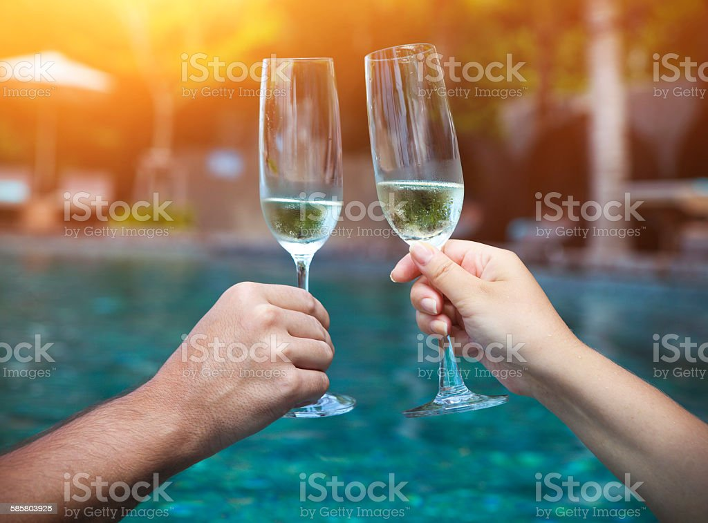 Couple holding glasses of champagne making a toast stock photo