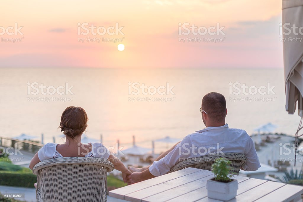 couple holding hands and enjoying the sunset on the beach stock photo