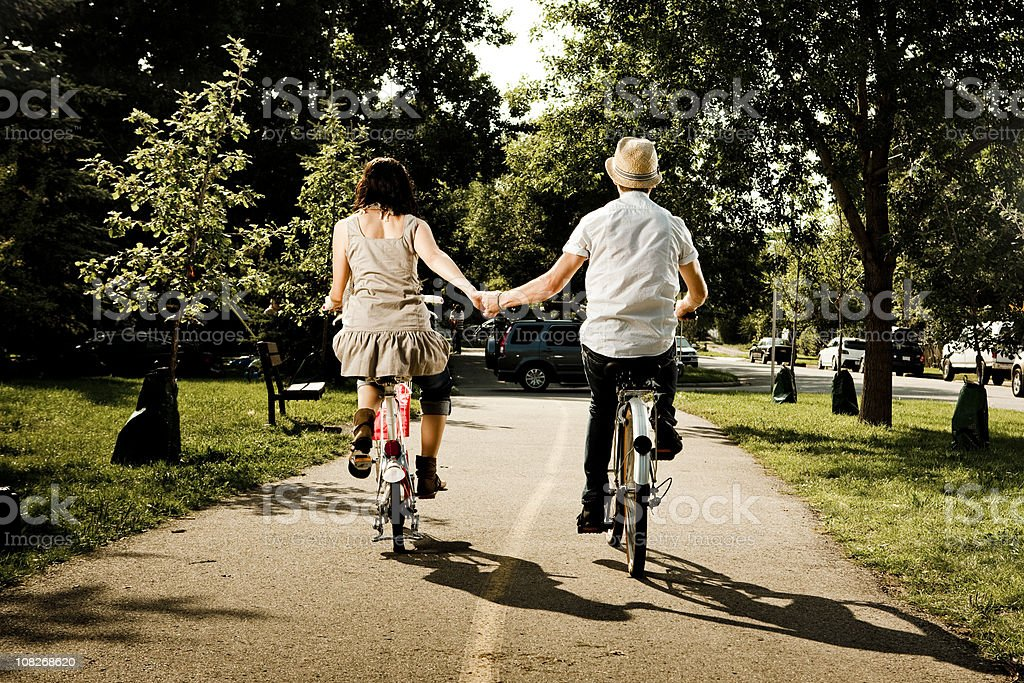 Couple holding hands and riding bikes royalty-free stock photo