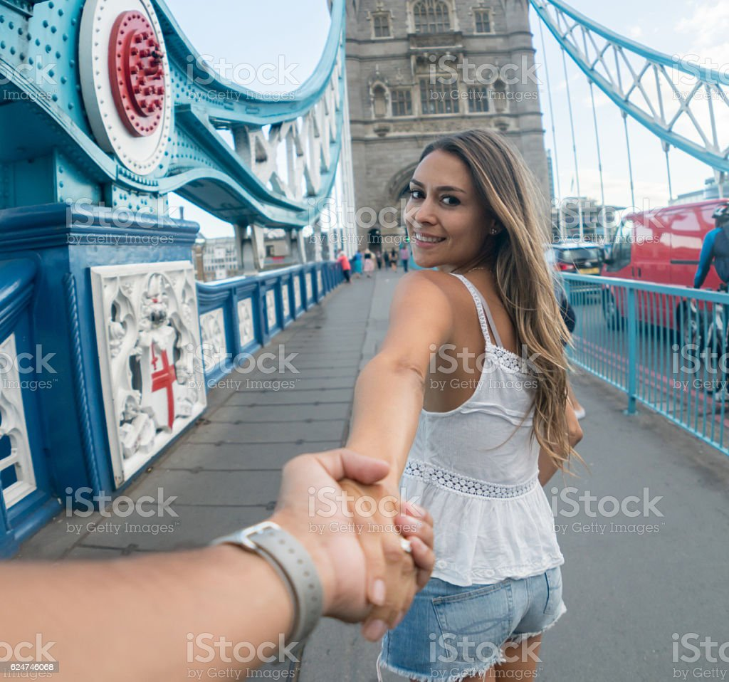Couple holding hands and traveling together stock photo