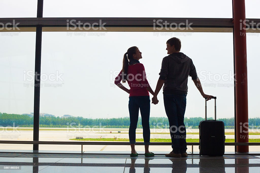 couple holding hands and waiting at airport terminal stock photo