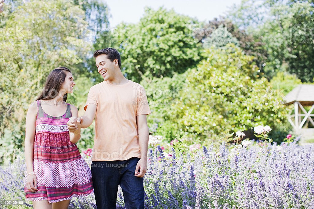 Couple holding hands and walking in park royalty-free stock photo