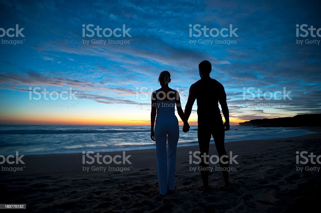 Couple holding hands at sunrise royalty-free stock photo