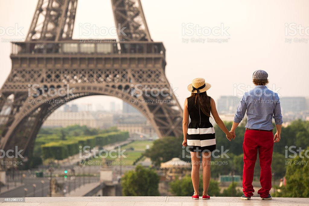 Couple holding hands at the Eiffel Tower in Paris stock photo