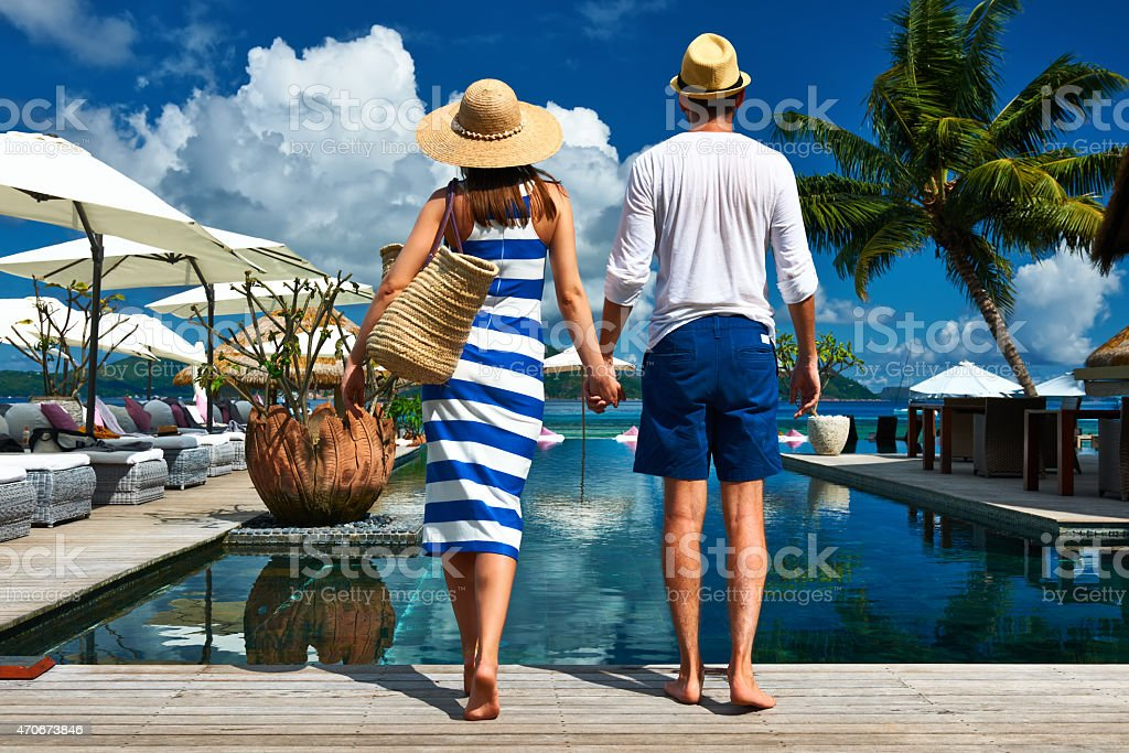 Couple holding hands at the poolside on a sunny day stock photo