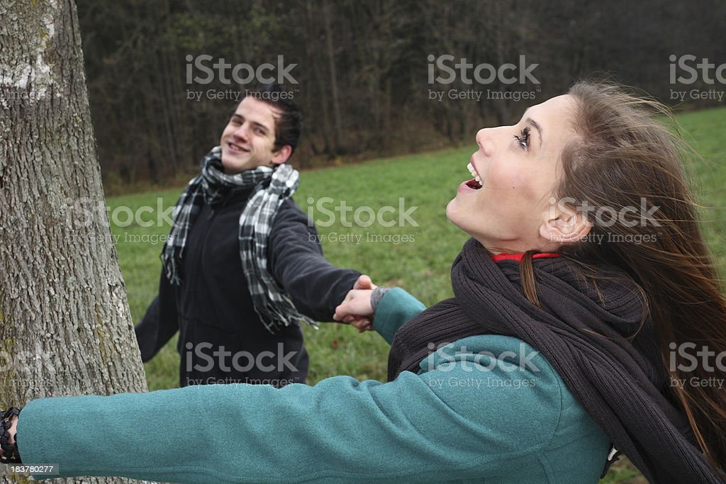 Couple holding hands beneath a tree stock photo