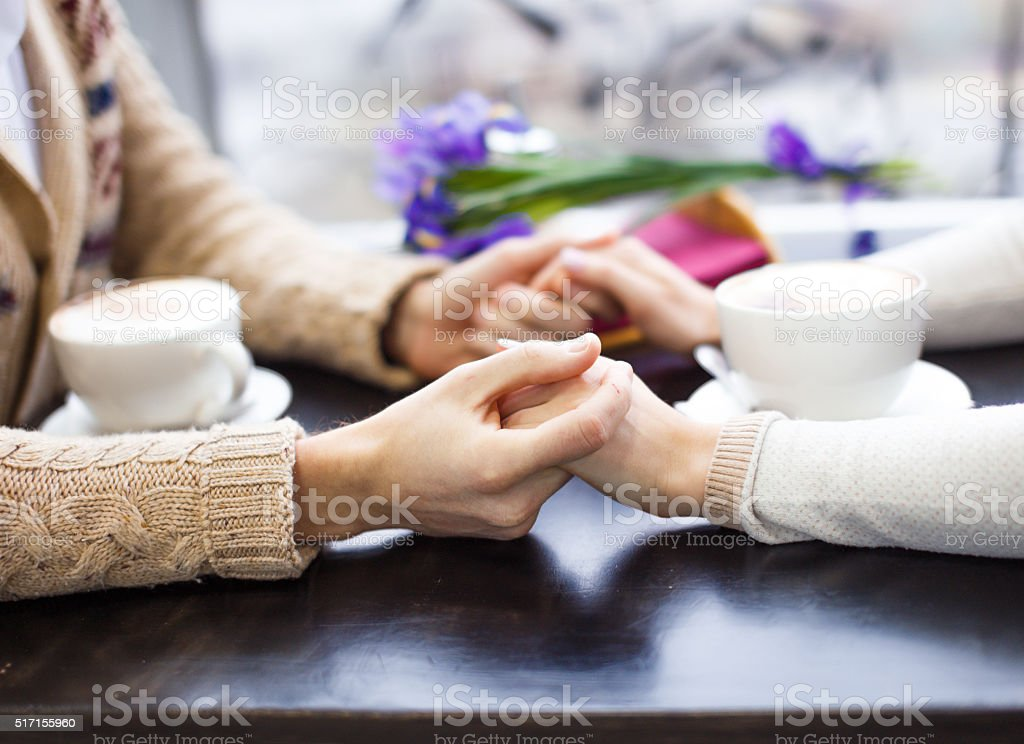 couple holding hands in a cafe stock photo