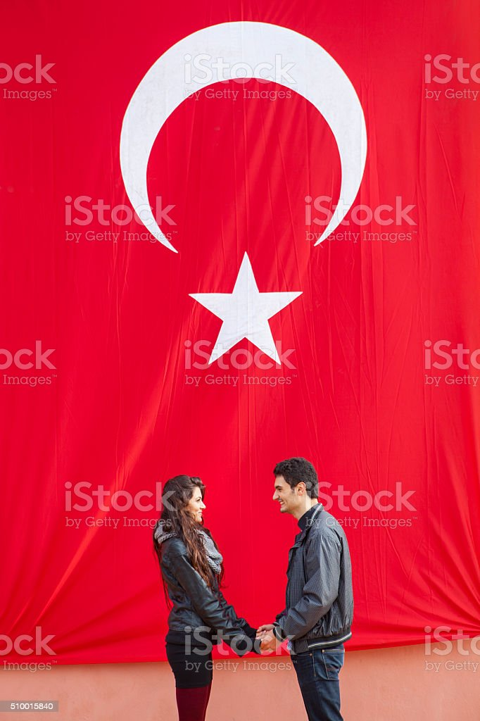 Couple Holding Hands In Front Of The Turkish Flag stock photo