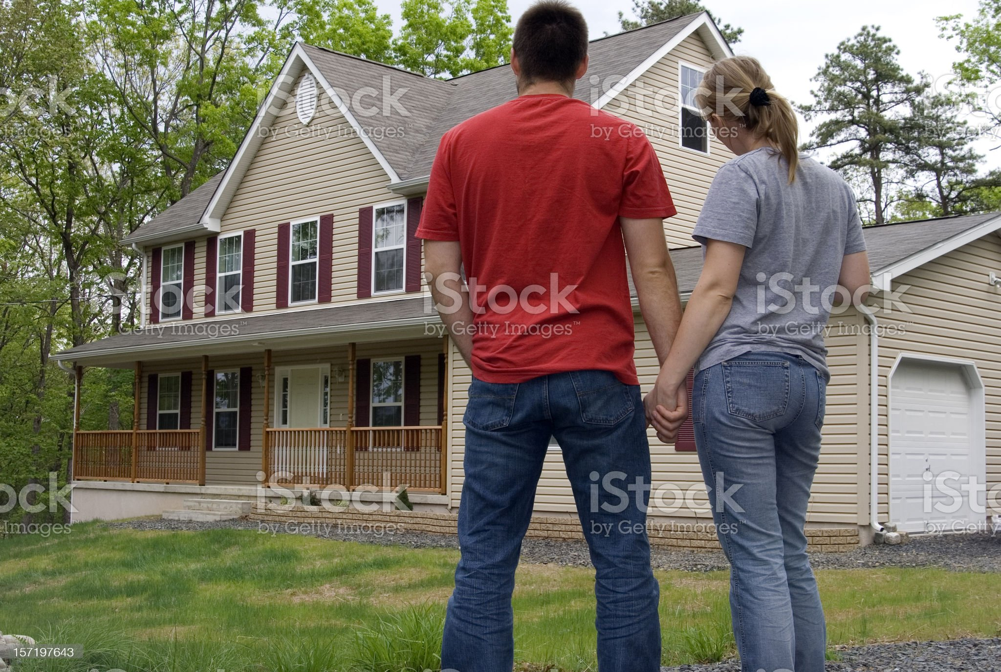 Couple holding hands in front of their new house royalty-free stock photo