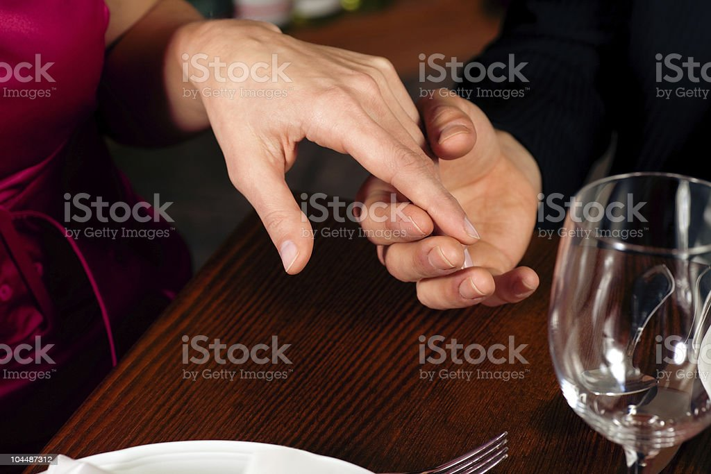 Couple holding hands on a restaurants table royalty-free stock photo
