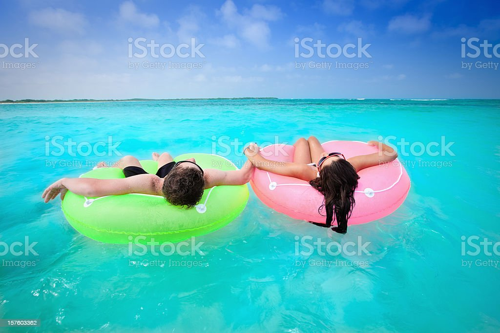 Couple holding hands on floating tubes stock photo