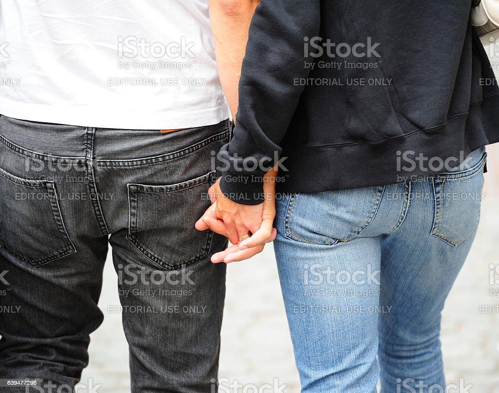 Couple holding hands on street Drottninggatan, Stockholm, Sweden stock photo