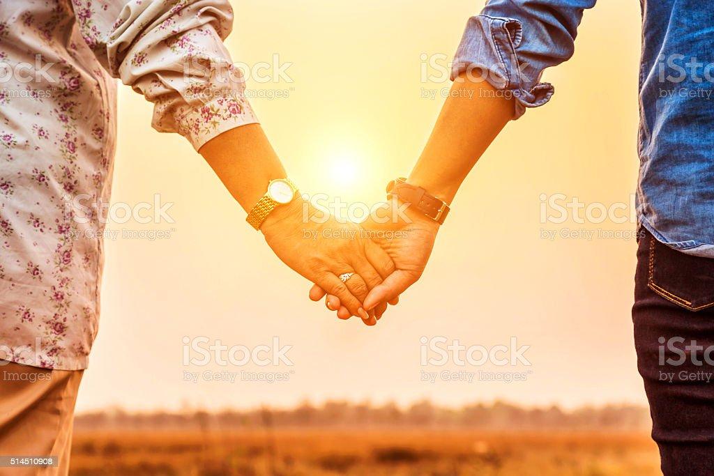 Couple holding hands on sunset background. stock photo