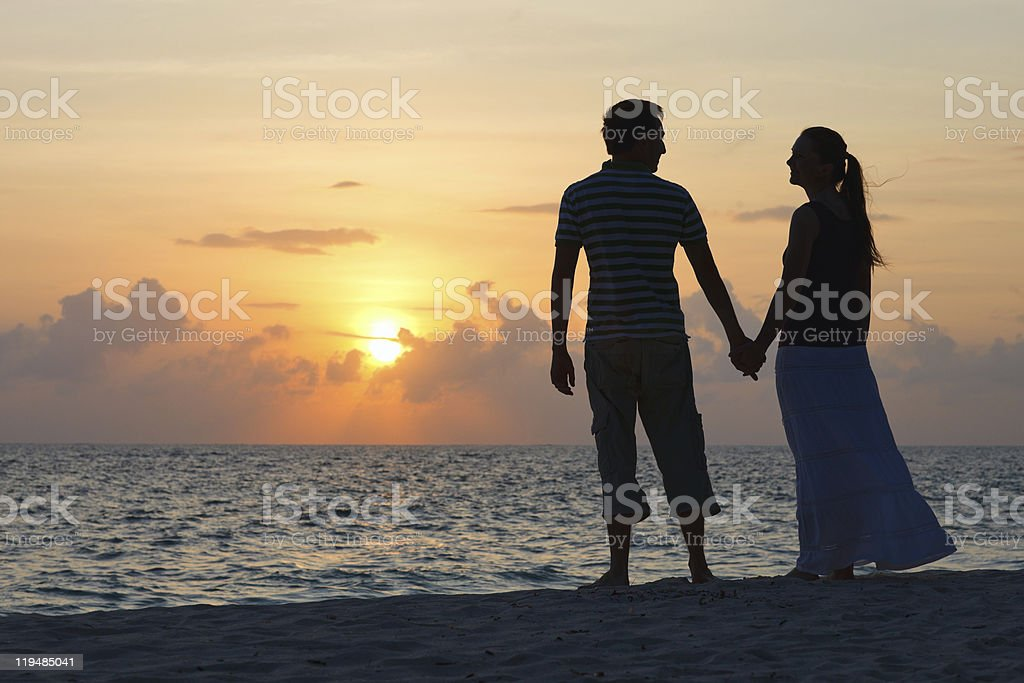 A couple holding hands on the beach at sunset  stock photo