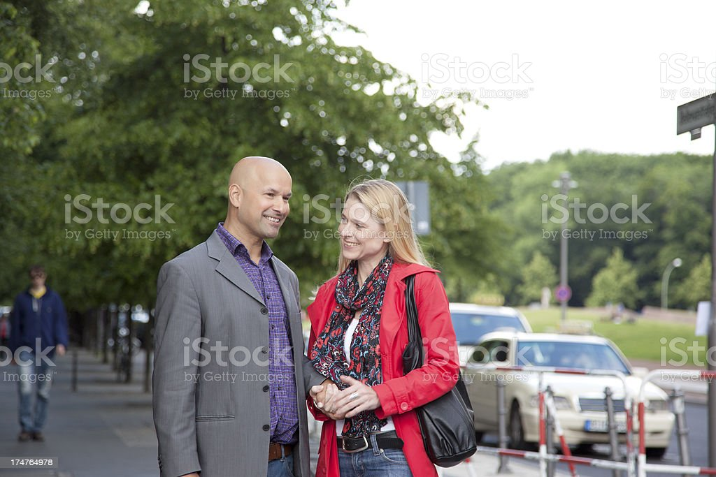 Couple holding hands on the sidewalk royalty-free stock photo