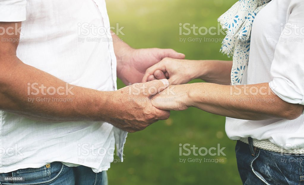 Couple holding hands outdoors stock photo