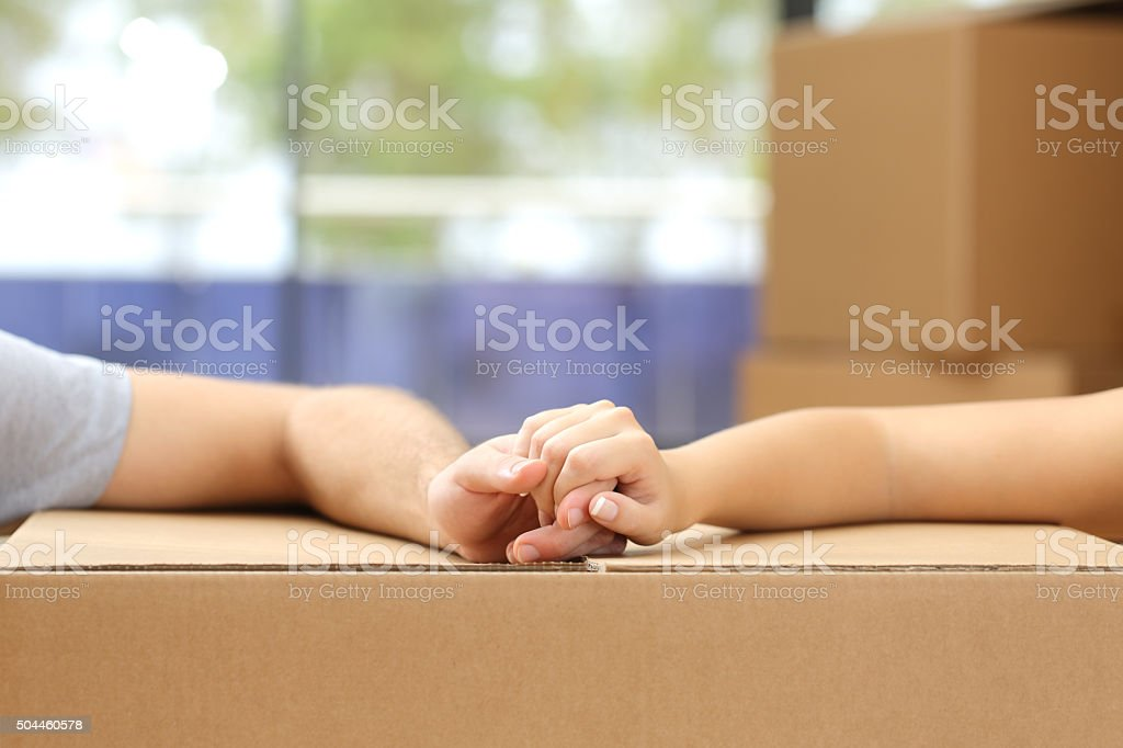 Couple holding hands over a box moving home stock photo