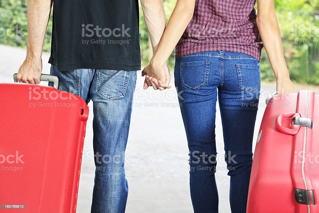 Couple holding hands pulling red suitcases outside royalty-free stock photo